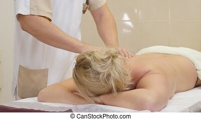 people, beauty, spa, healthy lifestyle and relaxation concept - close up of beautiful woman lying and having hand massage in spa