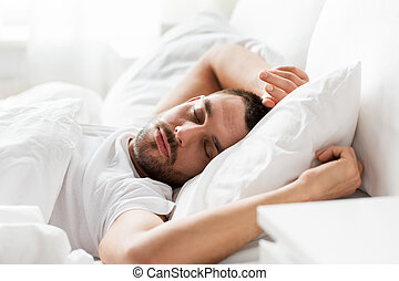 man sleeping in bed at home - people, bedtime and rest...
