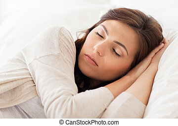 young woman sleeping in bed at home