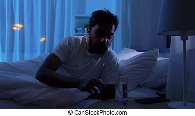 people, bedtime and thirst concept - sleepy indian man awaking at night and drinking water at home