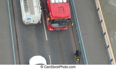 People bus and cars passing on the bridge