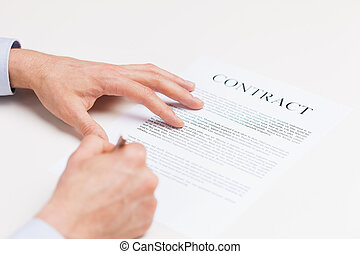 close up of male hands signing contract document