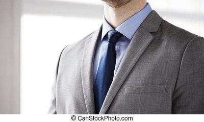 close up of man in suit adjusting necktie