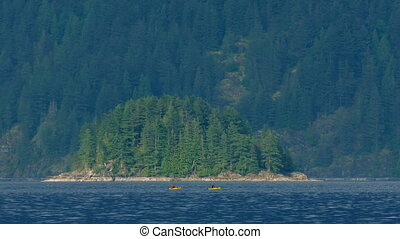 People Canoe Near Small Island In Rugged Landscape - Couple...