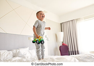 happy little boy with toy car on home or hotel bed