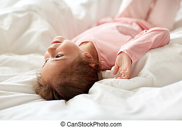 happy little girl lying in bed at home