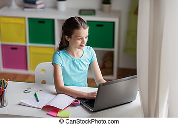 happy girl typing on laptop at home