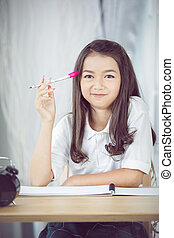 People, children, education and learning concept - happy girl with book and notebook
