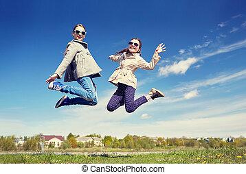 happy little girls jumping high outdoors