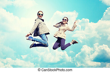 happy little girls jumping high over blue sky