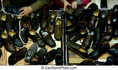 People choose shoes at stall,Various varieties of styles.