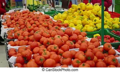 people chooses vegetables tomatos in supermarket