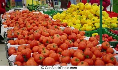 people chooses vegetables tomatos in supermarket