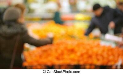 People choosing fruit in supermarket out of focus