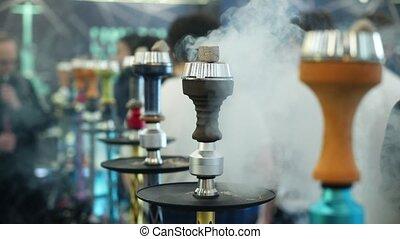 People choosing hookah. Smoking tobacco at exhibition. Shisha bowl