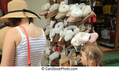People choosing slippers at street shop