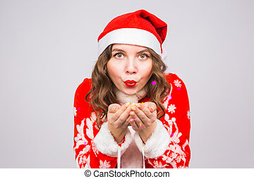 People, christmas and holidays concept - pretty young lady in santa claus costume blowing confetti on white background