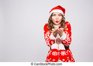 People, christmas and holidays concept - pretty young lady in santa claus costume blowing confetti on white background with copy space