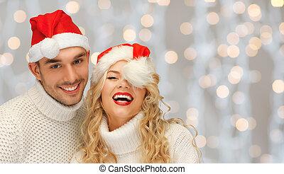happy family couple in sweaters and santa hats - people,...