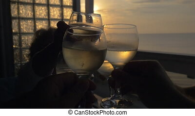 People clanging glasses in outdoor terrace at sunset