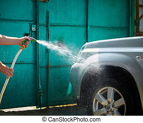 People cleaning car using high pressure water