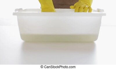 woman washing and squeezing rag in basin at home - people,...