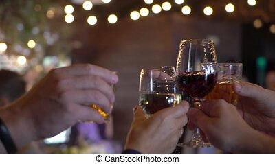 People clink glasses with wine and champagne after toast at...