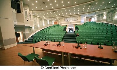 people comes out from conference hall with green seats,...