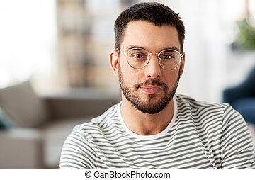 portrait of man in glasses at home