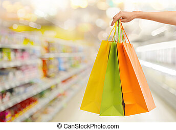 hand with shopping bags over supermarket