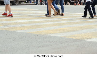 People cross the road at a pedestrian crossing. City life