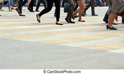 People cross the road at a pedestrian crossing.