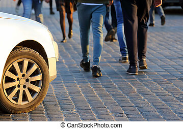 people cross the road in front of the car