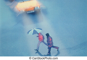 High angle view of two men walking across a street in the rain in front of a yellow car. One of the people has an umbrella. Horizontal shot.