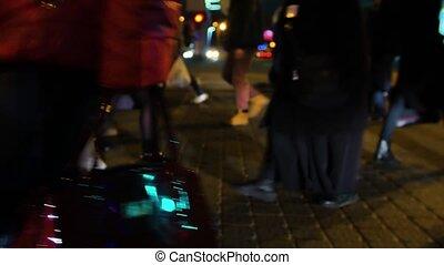 people crossing crosswalk in city. new york city night lights background