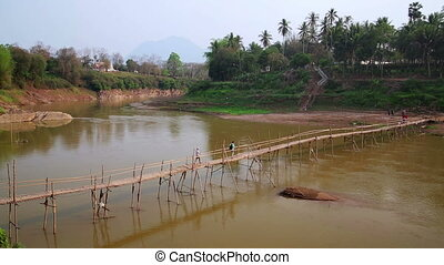 People crossing river on bamboo bridge, luang prabang, laos