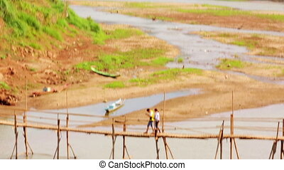 People crossing river on bamboo bridge, luang prabang, laos