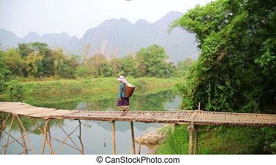 People crossing river on bamboo bridge, vang vieng, laos
