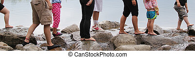 People crossing rocks with stream - Bare feet on rocks with ...