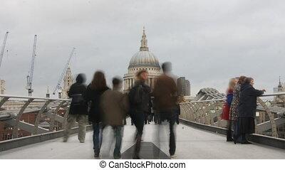 people crossing the millenium bridge, london, uk