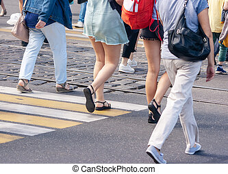 people crossing the street at pedestrian crossing on sunny