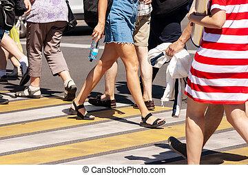 people crossing the street at pedestrian crossing