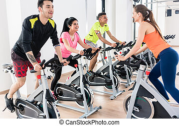 People cycling at gym