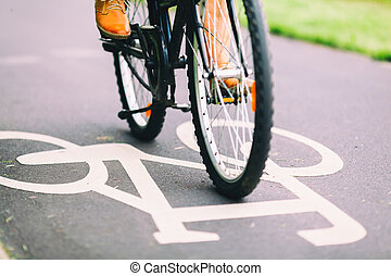 City bike sign on asphalt bikepath man cycling on road, colorful vintage light on street, commuting to work on bicycle in urban environment
