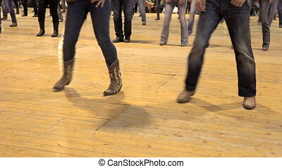 People dancing cowboy line dance at a folk country event, USA style