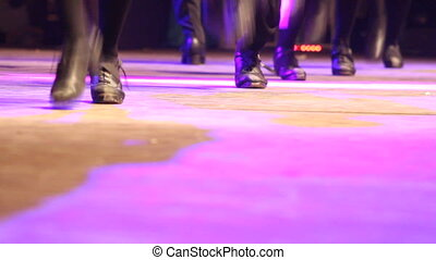 Two rows of people doing Irish dance with traditional step shoes. Close up double line of female dancing feet on stage became one. Music, tradition and culture of Ireland. Celtic show on wooden floor