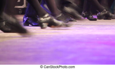 People dancing Irish dance on stage with traditional step...