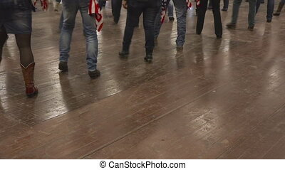 People dancing line dance at country show with USA flag -...