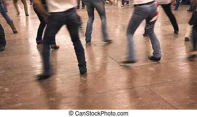 People dancing together at a?hoedown?party. Denim, cowboy...