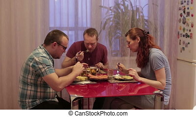 People dine at the table - Two men and a woman sitting at a...